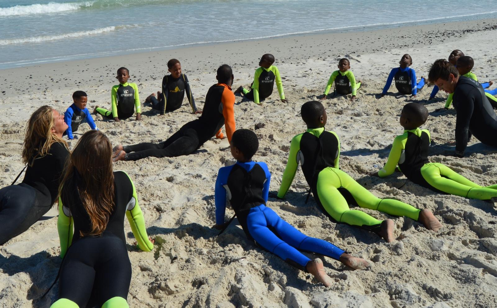 Volunteers and South African children stretch on a surfing program for last minute volunteering abroad.